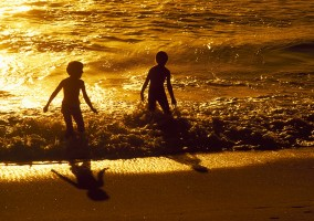 Children Playing In The Ocean At Sunset